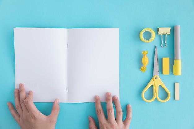 La mano de una persona que sostiene la página en blanco con efectos de escritorio y dulces en el contexto azul