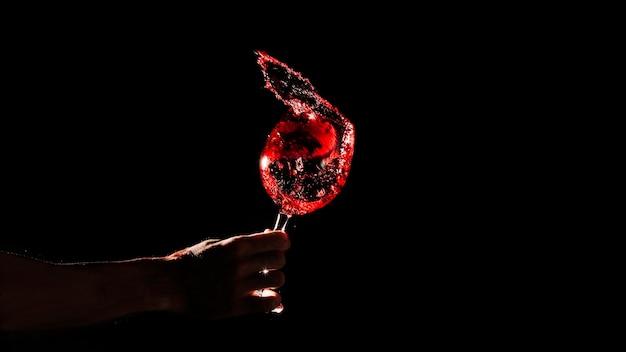 Mano de la persona que sostiene el vaso de vino rojo sobre fondo negro
