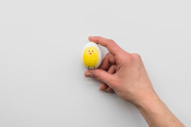 Mano de persona sosteniendo huevo con empate