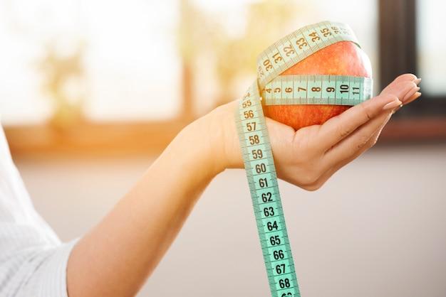 Mano de la persona sosteniendo una manzana roja con cinta de medición verde