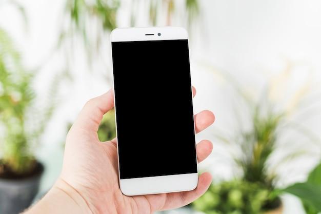 La mano de una persona sosteniendo un teléfono inteligente.