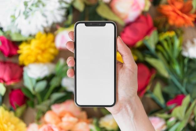 Mano de la persona con el teléfono inteligente cerca de las flores