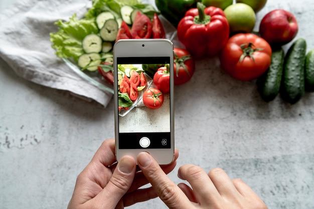 Una mano de persona tomando foto de vegetales frescos en el fondo