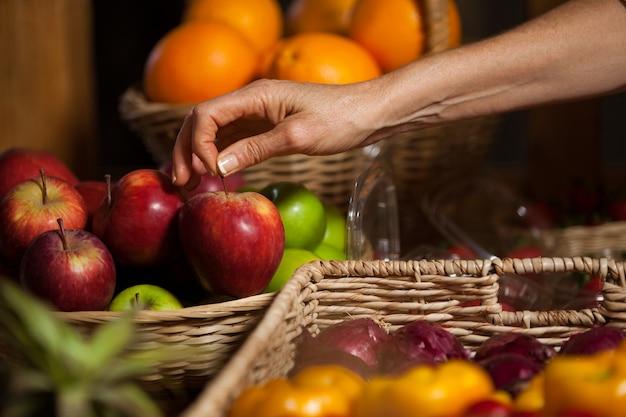 Mano de personal femenino sosteniendo manzanas en la sección orgánica