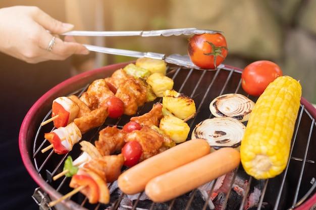 Mano de personas y colorido asado a la parrilla con carne de cerdo, salchichas, tomate, cebolla, piña, chile y maíz en barbacoa portátil al aire libre.