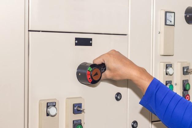 Mano de personas modo de selección del interruptor de llave en el panel de control eléctrico para operar la máquina industrial