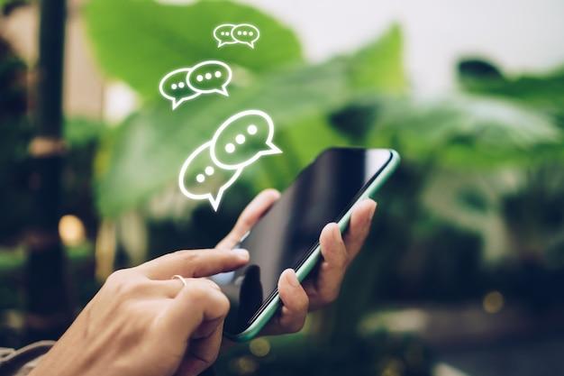 La mano de personas que usa el teléfono inteligente escribiendo, chateando o mensajes de texto en los íconos de chat aparecen.