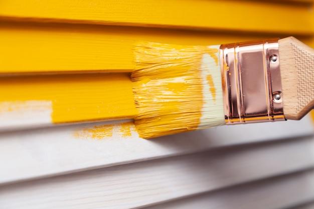 Mano con pincel pintando puerta de madera natural con pintura amarilla