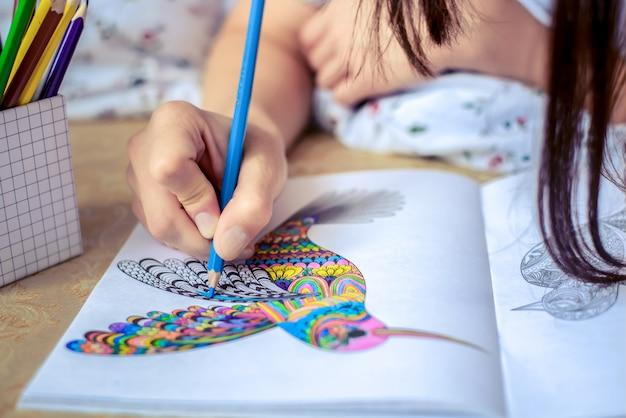 La mano pinta la imagen con lápiz de color