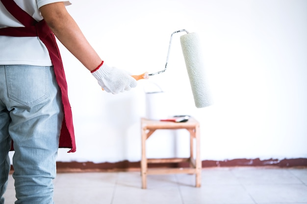 Mano del pintor en la pared blanca de la pintura del guante con el rodillo de pintura en sitio, forma y estructura