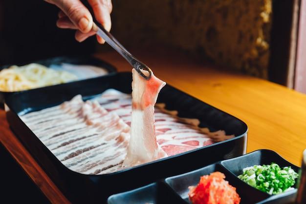 Una mano pizca slice kurobuta cerdo con textura de mármol con palillos