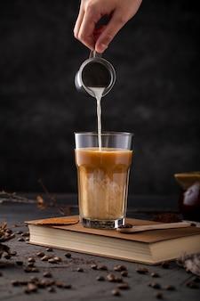 Mano plana laica vertiendo leche en café