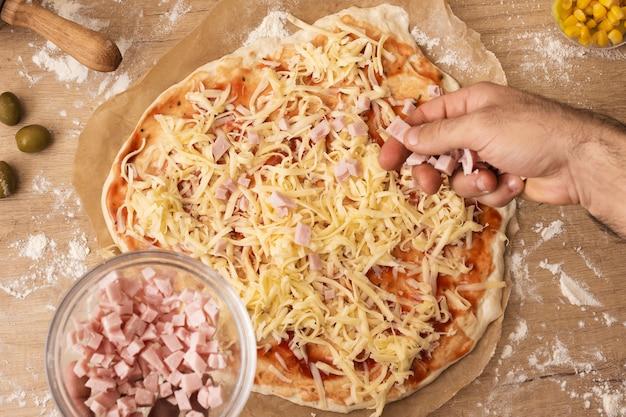 Mano plana pone asar jamón sobre masa de pizza