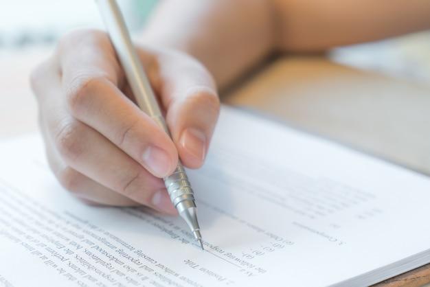 Mano con la pluma sobre el formulario de solicitud