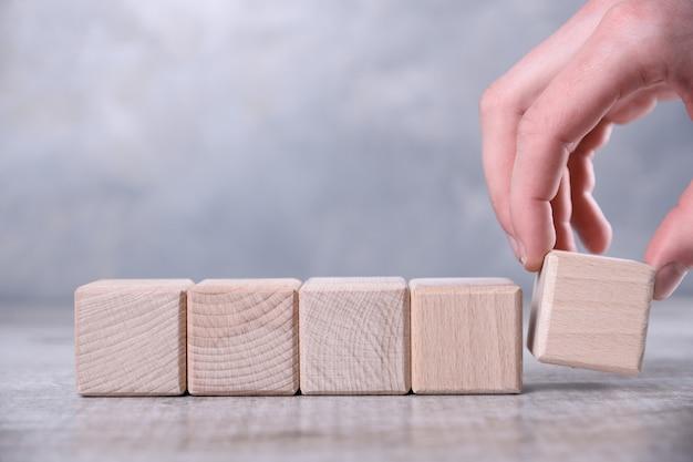 La mano pone el cubo de madera en blanco con espacio para su palabra, letra, símbolo sobre la mesa. lugar para texto, espacio de copia libre