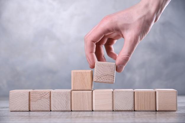 La mano pone un cubo de madera en blanco con espacio para tu palabra