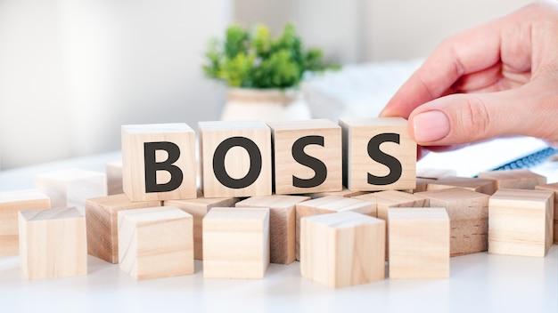 La mano pone un cubo de madera con la letra s de la palabra boss. la palabra está escrita en cubos de madera sobre la superficie blanca de la mesa. conceptos de comunicación y negocios