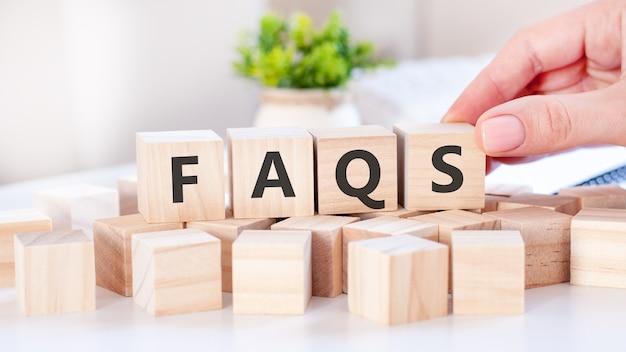 La mano pone un cubo de madera con la letra s de la palabra faqs. la palabra está escrita en cubos de madera sobre la superficie blanca de la mesa. conceptos de comunicación y negocios