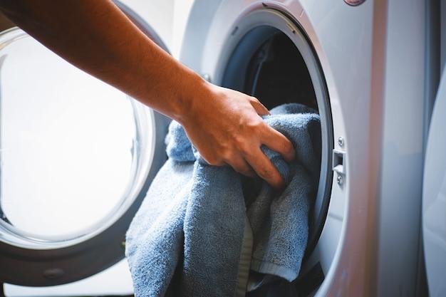 Mano y pone la ropa en la lavadora