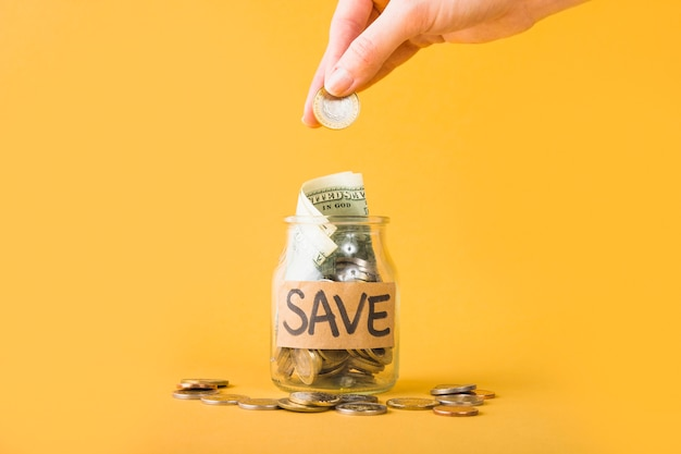 Mano poner monedas en jarra para ahorrar