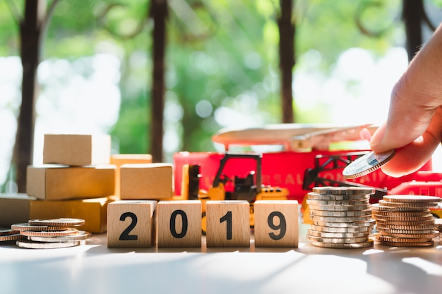 Mano poner monedas en vehículo de transporte y bloque de madera 2019
