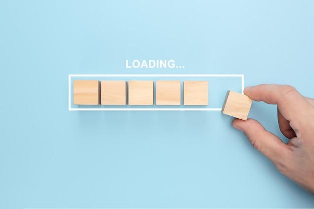 Mano poniendo cubo de madera en la barra de carga de infografía virtual con texto de carga.