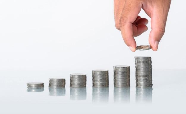 Mano poniendo dinero monedas pila creciendo en blanco