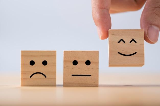 Mano poniendo emoción sonriente entre emoción normal y triste que imprime la pantalla en madera cúbica. encuesta de experiencia del cliente y concepto de comentarios de satisfacción.