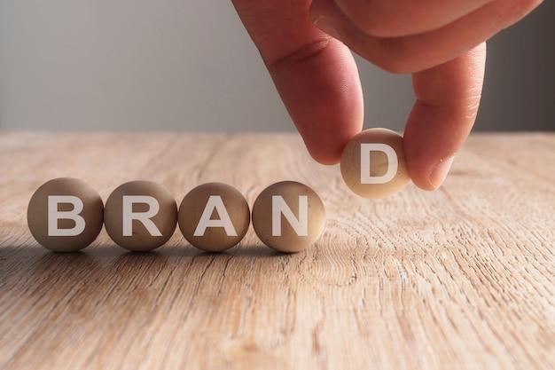 Mano poniendo en la palabra de la marca escrita en bola de madera