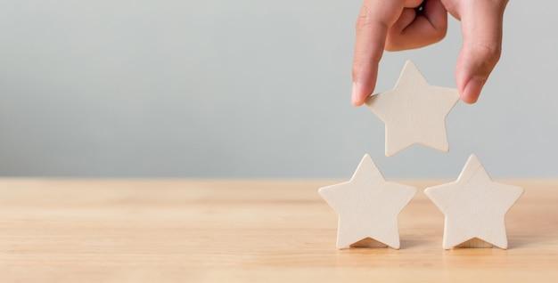 Mano poniendo forma de cinco estrellas de madera en la mesa
