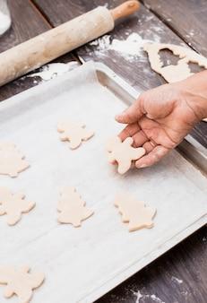 Mano poniendo hombre en forma de pastelería en una bandeja para hornear