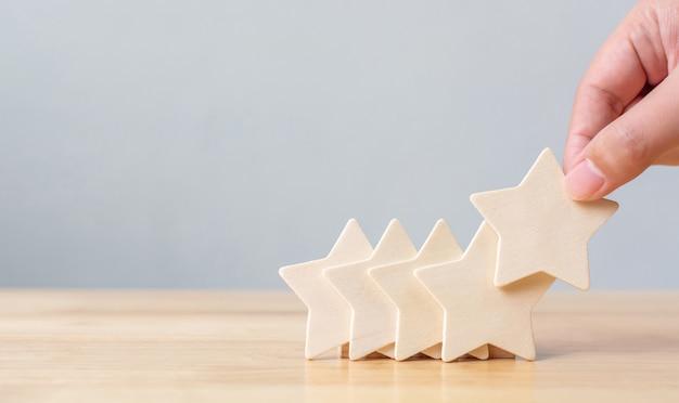 Mano poniendo madera de cinco estrellas en la mesa. el mejor concepto de experiencia de cliente de calificación de servicios empresariales excelente