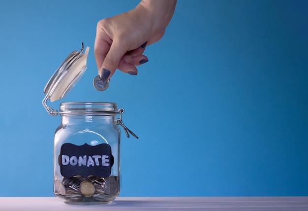 Mano poniendo una moneda en un frasco de vidrio con monedas con una etiqueta de donación de tiza sobre una superficie azul