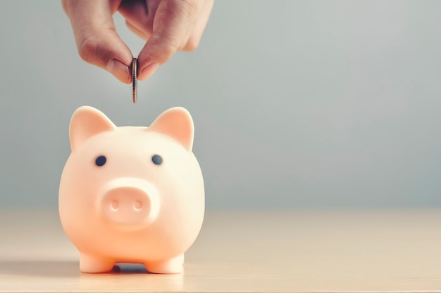 Mano poniendo monedas con una alcancía o caja de dinero en un piso de madera para ahorrar dinero para la inversión.