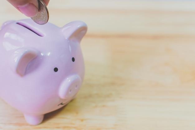 Mano poniendo monedas en la hucha. concepto de ahorro de inversión financiera de dinero