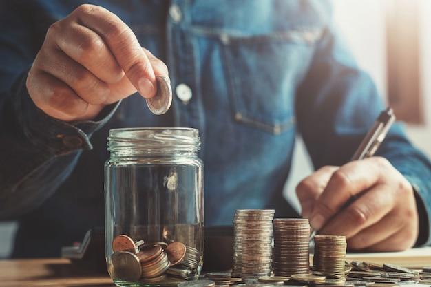 Mano poniendo monedas en vaso de jarra para ahorrar dinero finanzas y concepto de contabilidad