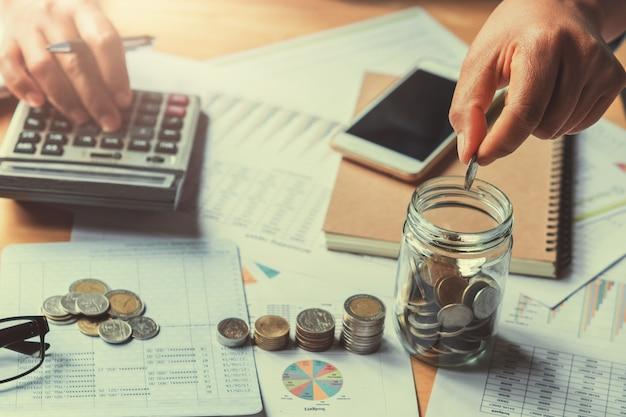 Mano poniendo monedas en vidrio. cocept ahorro de dinero finanzas contabilidad