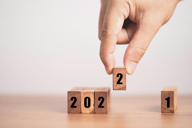 Mano poniendo el número dos para reemplazar el número uno para cambiar el año 2021 al 2022. feliz navidad y próspero año nuevo concepto.