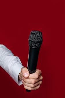 La mano de un presentador masculino, reportero, periodista sostiene un micrófono en una pared roja