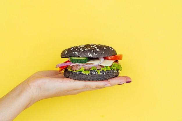 Mano presentando sabrosa hamburguesa con queso