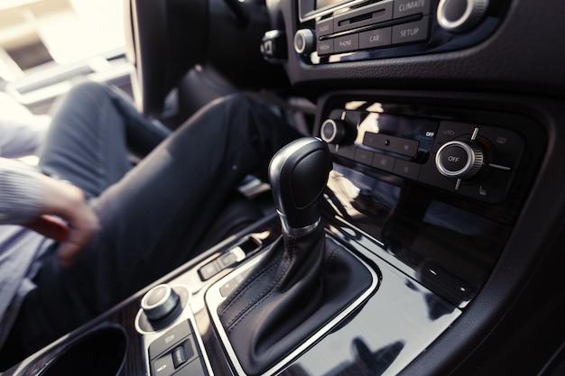 Mano presionando el botón de encendido para encender el sistema estéreo del auto