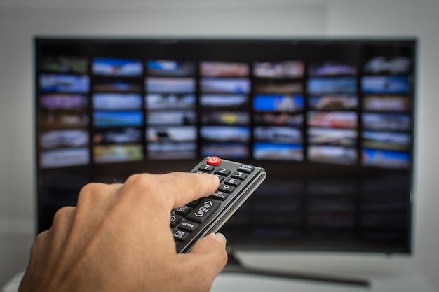 Mano presionando el control remoto de la televisión inteligente
