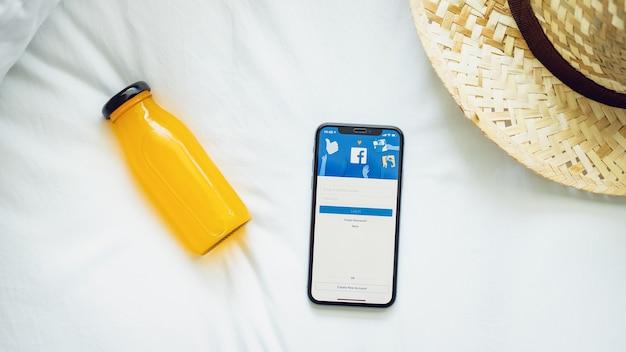 La mano está presionando la pantalla de facebook en apple iphone x, las redes sociales están usando para obtener información.