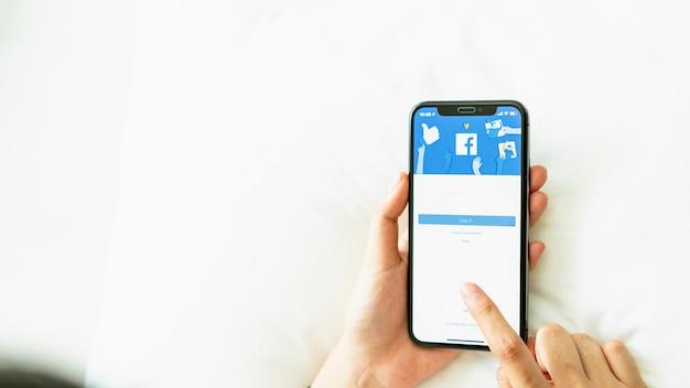 La mano está presionando la pantalla de facebook.