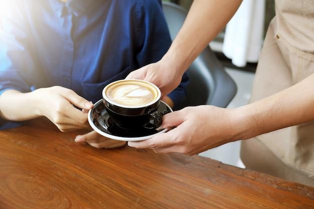 Mano del primer de una camarera que sirve una taza de café al cliente.