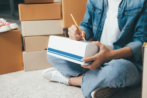 Mano del primer de la dirección de la escritura de la mujer joven en la caja del paquete para la orden de entrega al cliente, envío y logística, comerciante en línea y vendedor, dueño del negocio o pyme, compras en línea.