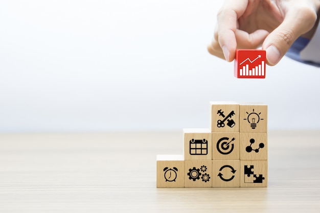 La mano del primer elige los bloques de madera apilados con el icono del gráfico en otros iconos del negocio.