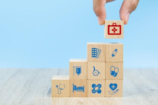 La mano del primer elige los bloques de madera del juguete de la forma del cubo apilados con el icono de la bolsa del equipo médico.