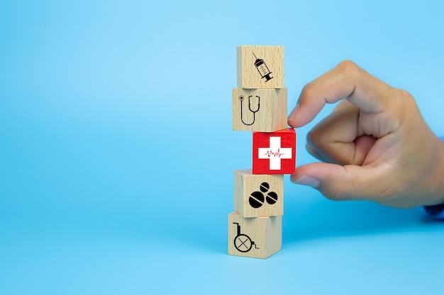 La mano del primer elige un cubo de bloques de juguete de madera con un icono de ritmo cardíaco de la cruz roja apilados para conceptos médicos y de seguro de salud.