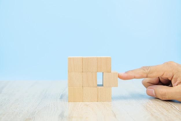 La mano del primer elige un juguete del bloque de madera de la forma del cubo apilado sin gráfico.